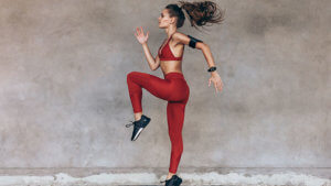 Woman in red activewear doing a knee lift