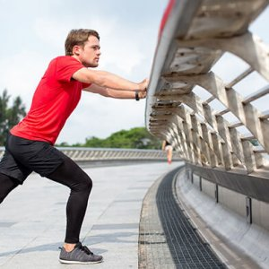 Man in compression leggings stretching his legs on a bridge