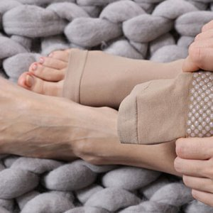 Person with varicose veins putting on toeless compression stockings