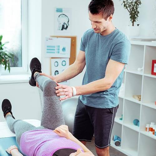 Male physical trainer helping a female patient stretch in his office