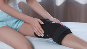 Woman sitting on a bed holding her knee covered in a knee brace