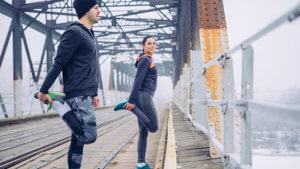 Man and woman in compression leggings stretching on a bridge