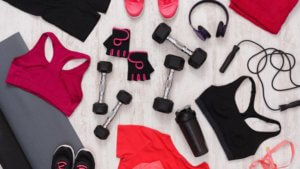 Assortment of women's activewear and exercise equipment spread out on a floor