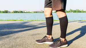 Man standing on a running path in leg compression sleeves