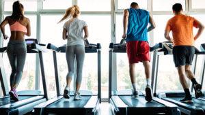 Group of men and women running on treadmills