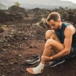 Man sitting on a trail wrapping his foot in compression tape