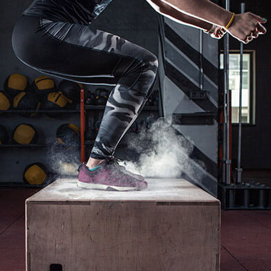 Person in compression leggings landing a box jump